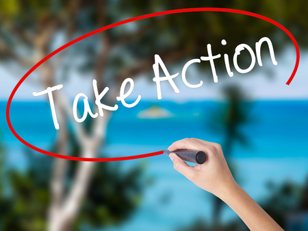 Woman Hand Writing Take Action with black marker on visual screen. Isolated on nature. Business concept. Stock Photo