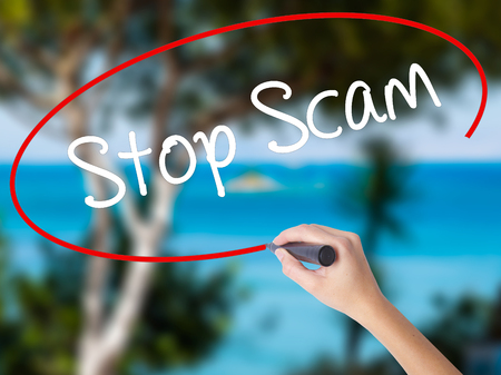 adware: Woman Hand Writing Stop Scam with black marker on visual screen. Isolated on nature. Business concept. Stock Photo Stock Photo