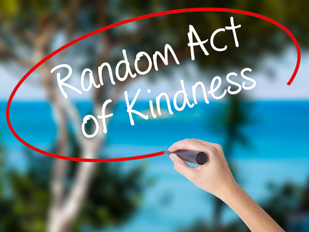 Woman Hand Writing Random Act of Kindness with black marker on visual screen. Isolated on nature. Business concept. Stock Photo