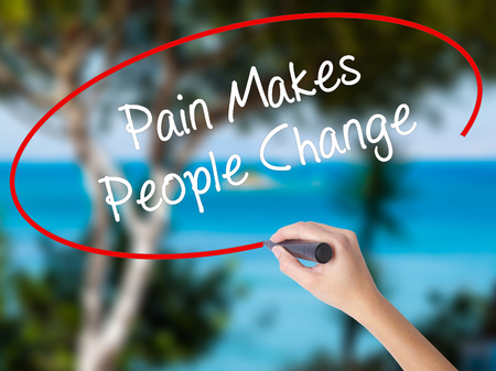 Woman Hand Writing Pain Makes People Change  with black marker on visual screen. Isolated on nature. Business concept. Stock Photo