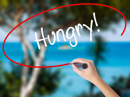 Woman Hand Writing Hungry! with black marker on visual screen. Isolated on nature. Business concept. Stock Photo