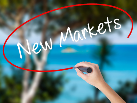 Woman Hand Writing New Markets with black marker on visual screen. Isolated on nature. Business concept. Stock Photo