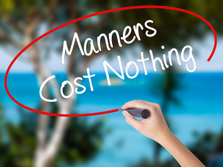 Woman Hand Writing Manners Cost Nothing with black marker on visual screen. Isolated on nature. Business concept. Stock Photo