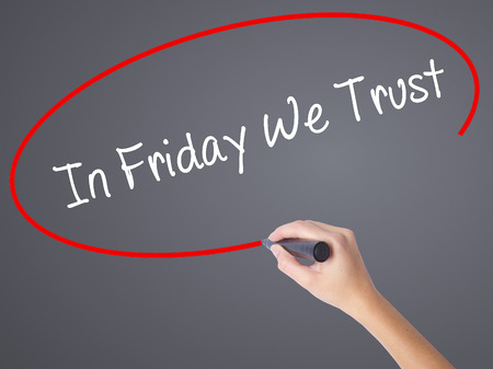 positiveness: Woman Hand Writing In Friday We Trust  with black marker on visual screen. Isolated on grey. Business concept. Stock Photo Stock Photo