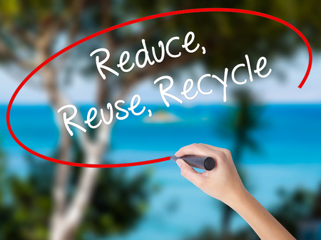 reduce reutiliza recicla: Woman Hand Writing Reduce Reuse Recycle with black marker on visual screen. Isolated on nature. Business concept. Stock Photo