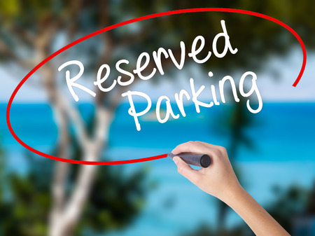 valet: Woman Hand Writing Reserved Parking with black marker on visual screen. Isolated on nature. Business concept. Stock Photo