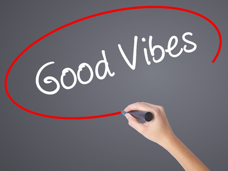 vibrations: Woman Hand Writing Good Vibes with black marker on visual screen. Isolated on grey. Business concept. Stock Photo Stock Photo