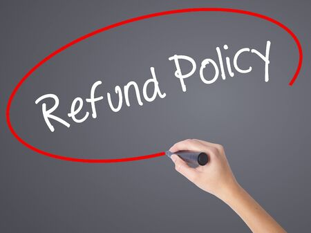 Woman Hand Writing Refund Policy with black marker on visual screen. Isolated on grey. Business concept. Stock Photo