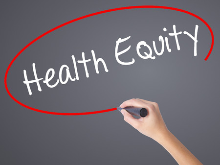 health equity: Woman Hand Writing Health Equityt with black marker on visual screen. Isolated on grey. Business concept. Stock Photo Stock Photo