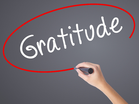 payer: Woman Hand Writing Gratitude with black marker on visual screen. Isolated on grey. Business concept. Stock Photo