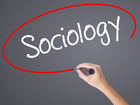 sociologia: Woman Hand Writing Sociology  with black marker on visual screen. Isolated on grey. Business concept. Stock Photo Foto de archivo