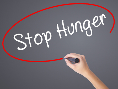dearth: Woman Hand Writing  Stop Hunger with black marker on visual screen. Isolated on grey. Business concept. Stock Photo