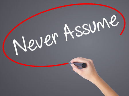 assume: Woman Hand Writing Never Assume with black marker on visual screen. Isolated on grey. Business concept. Stock Photo
