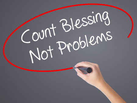 blessings: Woman Hand Writing Count Blessing Not Problems with black marker on visual screen. Isolated on grey. Business concept. Stock Photo