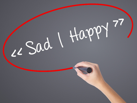 vibe: Woman Hand Writing Sad - Happy with black marker on visual screen. Isolated on grey. Business concept. Stock Photo