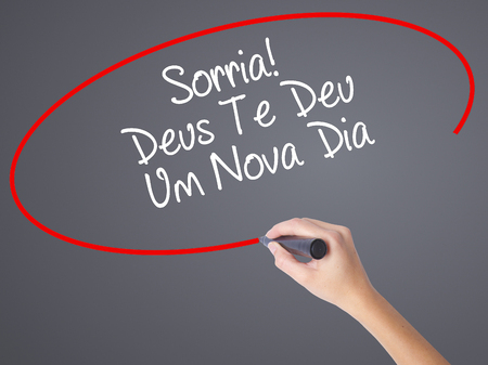 Woman Hand Writing Sorria! Deus Te Deu Um Novo Dia (Smile! God Gives You Another Day in Portuguese) with black marker on visual screen. Isolated on grey. Business,  internet concept. Stock Photo