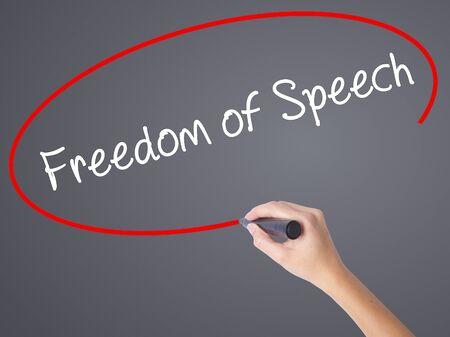 Escritura de la mano de la mujer Libertad de expresión con marcador negro en la pantalla visual. Aislado en gris Concepto de negocio. Foto de stock