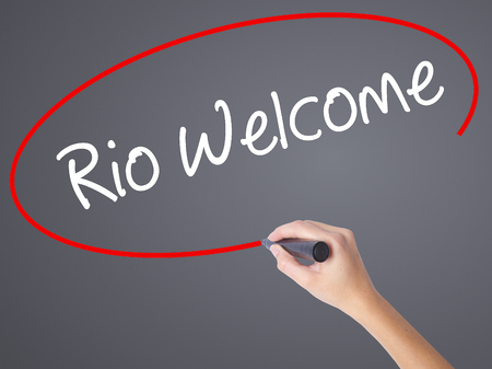 accommodating: Woman Hand Writing Rio Welcome with black marker on visual screen. Isolated on grey. Business, technology, internet concept. Stock  Photo
