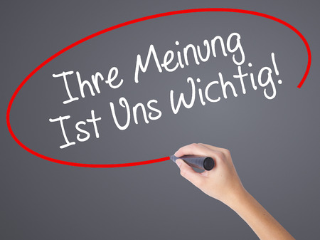 wichtig: Woman Hand Writing Ihre Meinung Ist Uns Wichtig! (Your Opinion is Important to Us in German) with marker on visual screen. Isolated on grey. Business concept. Stock Photo