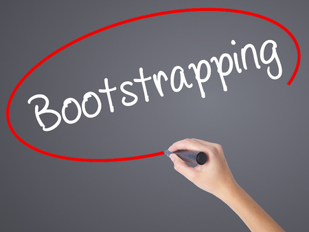 bootstrap: Woman Hand Writing Bootstrapping with black marker on visual screen. Isolated on grey. Business concept. Stock Photo