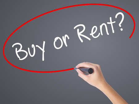 buying questions: Woman Hand Writing Buy or Rent? with black marker on visual screen. Isolated on grey. Business concept. Stock Photo