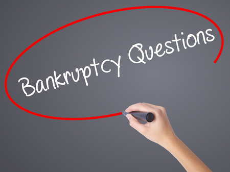 portable failure: Woman Hand Writing Bankruptcy Questions with black marker on visual screen. Isolated on grey. Business concept. Stock Photo