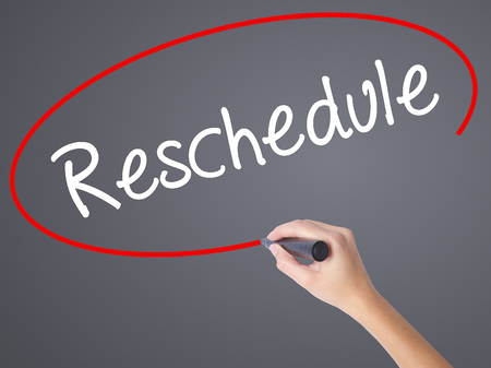 rescheduling: Woman Hand Writing Reschedule  with black marker on visual screen. Isolated on grey. Business concept. Stock Photo
