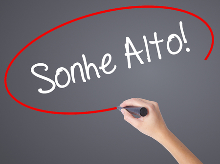 Woman Hand Writing Sonhe Alto! (Dream Big in Portuguese) with black marker on visual screen. Isolated on grey. Business concept. Stock Photo