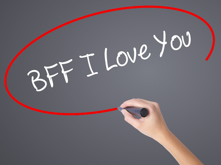 Woman Hand Writing BFF I Love You with black marker on visual screen. Isolated on grey. Business, technology, internet concept. Stock Photo