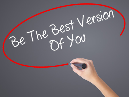 versions: Woman Hand Writing Be The Best Version Of You with black marker on visual screen. Isolated on grey. Business concept. Stock Photo
