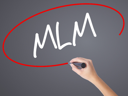 Woman Hand Writing  MLM (Multi-Level Marketing) with black marker on visual screen. Isolated on grey. Business concept. Stock Photo