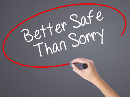 better safe than sorry: Woman Hand Writing Better Safe Than Sorry with black marker on visual screen. Isolated on grey. Business concept. Stock Photo