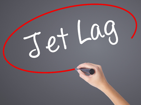 lag: Woman Hand Writing  Jet Lag with black marker on visual screen. Isolated on grey. Business concept. Stock Photo