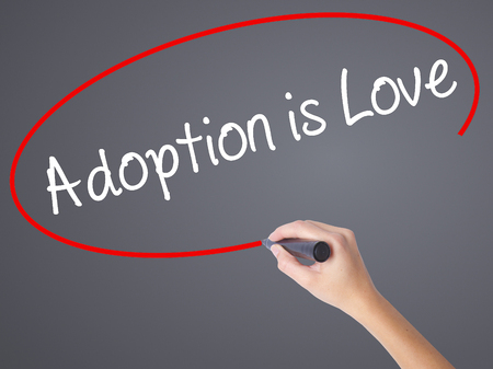 foster parenting: Woman Hand Writing Adoption is Love with black marker on visual screen. Isolated on grey. Adoption, technology, internet concept. Stock Photo