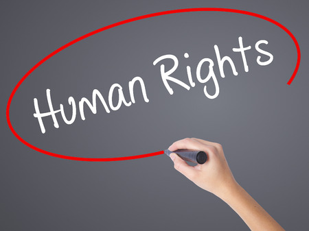 norms: Woman Hand Writing Human Rights with black marker on visual screen. Isolated on grey. Business concept. Stock Photo