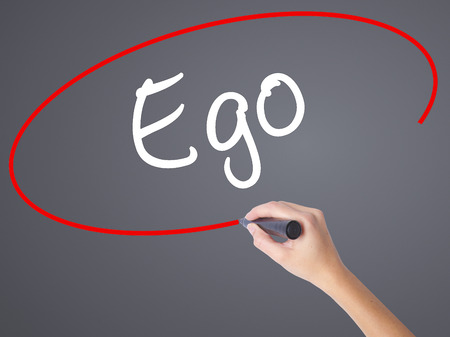 pretentious: Woman Hand Writing Ego with black marker on visual screen. Isolated on grey. Business concept. Stock Photo