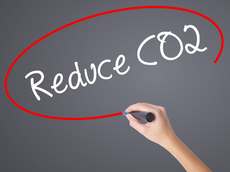 stop global warming: Woman Hand Writing Reduce CO2 with black marker on visual screen. Isolated on grey. Business concept. Stock Photo