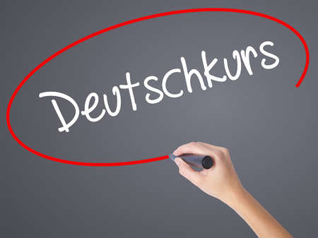 naturalization: Woman Hand Writing Deutschkurs (German Course in German) with black marker on visual screen. Isolated on grey. Business concept. Stock Photo Stock Photo