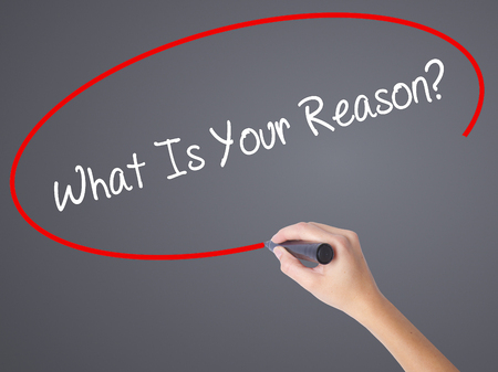Woman Hand Writing What Is Your Reason? with black marker on visual screen. Isolated on grey. Business concept. Stock Photo Stock Photo