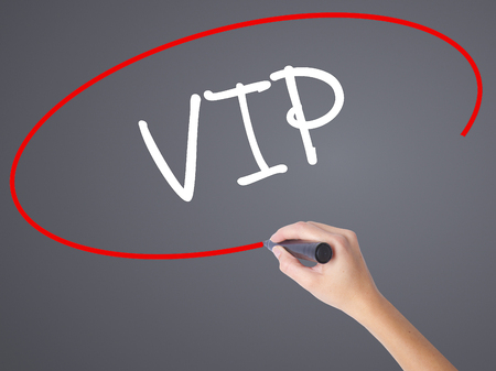 Woman Hand Writing  VIP with black marker on visual screen. Isolated on grey. Business concept. Stock Photo