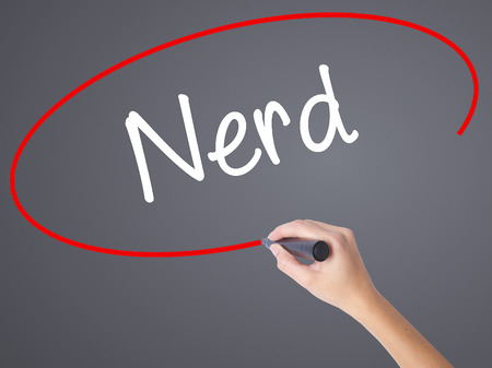qi: Woman Hand Writing Nerd with black marker on visual screen. Isolated on grey. Business concept. Stock Photo