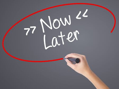 procrastination: Woman Hand Writing NowLater with black marker on visual screen. Isolated on grey. Business concept. Stock Photo