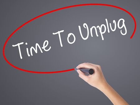 unplugging: Woman Hand Writing Time To Unplug with black marker on visual screen. Isolated on grey. Business concept. Stock Photo