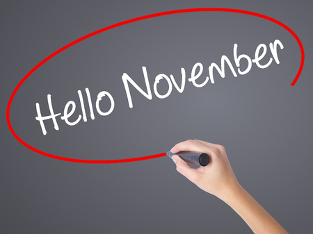 Woman Hand Writing Hello November with black marker on visual screen. Isolated on grey. Business concept. Stock Photo Stock Photo