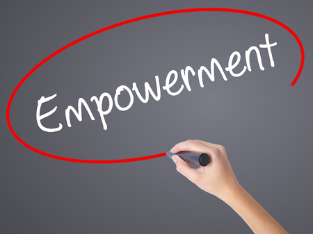 endow: Woman Hand Writing Empowerment with black marker on visual screen. Isolated on grey. Business concept. Stock Photo Stock Photo