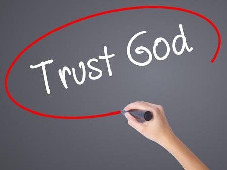 Vrouw Hand schrijven vertrouwen God met zwarte marker op visuele scherm. Geïsoleerd op grijs. Bedrijfsconcept. Stock foto