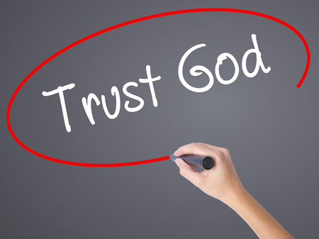 Woman Hand Writing Trust God  with black marker on visual screen. Isolated on grey. Business concept. Stock Photo