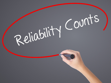 liable: Woman Hand Writing Reliability Counts with black marker on visual screen. Isolated on grey. Business, technology, internet concept.