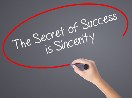 Woman Hand Writing The Secret of Success is Sincerity with black marker on visual screen. Isolated on grey. Business concept. Stock Photo