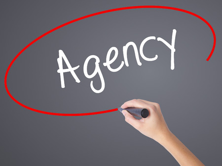 stock agency: Woman Hand Writing Agency with black marker on visual screen. Isolated on grey. Business concept. Stock Photo